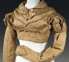 A SPENCER JACKET OF BRONZE SILK  EARLY 19TH CENTURY with V-shaped rouleaux trim to the bodice, with puffed shoulder detail.