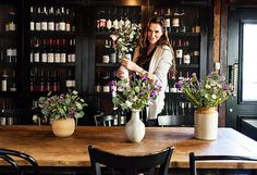 Claire arranges flowers in A.O.C's cozy private dining room, which houses thousands of bottles of wine.