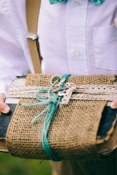 A family Bible wrapped with burlap and twine with rings tied to it adds an heirloom quality without having to spend $$ on a ring bearer's pillow... plus it's something that will be kept for a long time! :) photo by KD Burke Photography #rings #wedding #budget