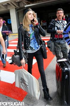 Cara Delevingne arrived in Nice wearing a black leather biker jacket with black skinny jeans, a printed tee, backwards baseball cap, and lace-up motorcycle boots. Delevigne Cara, Cara Delevingne Style, Cara Delevingne Paper Towns, Cara Delevingne Tattoo, Star Fashion, Look Fashion, Fashion Models, Fashion Photo, Sac Saint Laurent