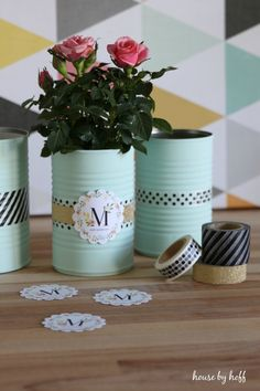Painted tin cans is an elegant container for potted roses.