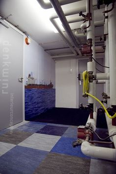 Combination of heating pipes with photo wallpaper oil tanker, gives a tough atmosphere at the staff room. Design: Denk Ruim Over Interieur