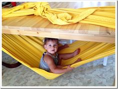 create a diy woven wrap hammock for your kiddo by tying a blanket around a table.