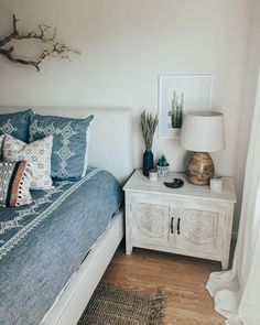 bohemian bedroom, anthropologie bedding, white washed wood table, carved wood bedside table, mudcloth pillows