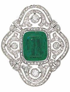 A BELLE EPOQUE EMERALD AND DIAMOND BROOCH, CIRCA 1915. Of curving quatrefoil design, the cushion shaped emerald centre to the pierced millegrain-set circular-cut diamond panel, 3.3cm wide. #BelleÉpoque #brooch