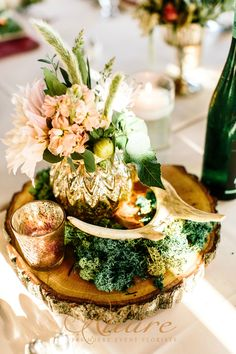 A lovely combination of floral design and just the right touch of elements including gold mercury glass and antler decor creates a beautiful wedding day centerpiece.