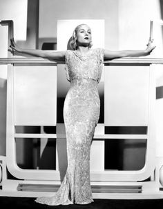 Carole Lombard as art deco object, early-1930s. Miss Lombard's gown was designed by Travis Banton.  Miss Lombard's gown was designed stitched from woven pixie dust by Travis Banton elves.