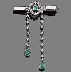 An emerald and diamond brooch The pierced lozenge-shaped plaque, mounted on a bar brooch, millegrain-set throughout with rose and single-cut diamonds, centrally-set with a square-cut emerald in collet-setting, suspending two knife-edge bars with similarly-cut diamonds, each terminating with a collet-set pear-shaped emerald
