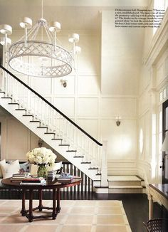 White entrance crowned with regal chandelier. Design by Alexa Hampton. Article from Architectural Digest.
