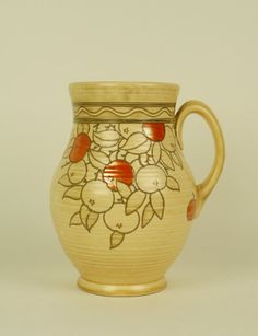 A Charlotte Rhead for Crown Ducal single handled vase, circa 1938-1940, decorated with a tube lined orange fruit pattern against a mushroom ground, impressed shape number 145 and printed marks (minor nibble to the rim), 26cm high