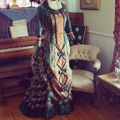 Bold plaid taffeta promenade gown with matched plaid ruffles and ruches, shirred chiffon front inset and knife pleated hem a la mode of 1876. Final fitting was at our historic home in Tombstone, AZ...the perfect setting for this Lily Absinthe original.