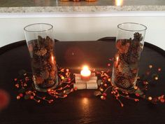 Pine cones cylinders with fall candle holder decorations at the base. Homemade cork coaster with a pumpkin spice teacup candle :) I love Fall!