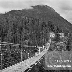 People walking on footbridge leading towards mountain