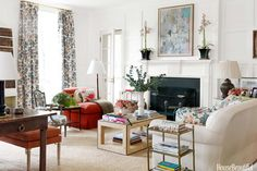 """Triple-hung windows and paneled walls provide a traditional framework in designer Connie Newberry's house in New York's Dutchess County. """"Sam MItchell did a great job with the architecture,"""" Newberry says. An overstuffed chair upholstered in orange wool boucle from Holly Hunt """"gives the living room some oomph"""" and picks up the brightest color in the Brunschwig & Fils chintz. A geometric coffee table, covered in grass cloth with leather piping adds a modern note. Sisal rug by Charlotte Mo..."""