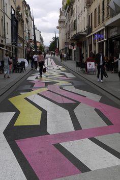 Une oeuvre colorée de Sabina Lang et Daniel Baumann qui ont créé des Street Painting c'est-à-dire une série de peintures aux formes géométriques et aux couleurs vives directement apposées sur l'asphalte de la rue.