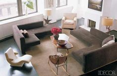 Living room of Julianne Moore - via Dering Hall: Actress Julianne Moore's West Village loft is modern comfort at its best. A neutral palette of brown and cream gives the star's home a calm, no-frills vibe. Vintage L-shaped sofas by Vladimir Kagan and a leather armchair from Furniture Co. provide ample seating, while driftwood table lamps add a rustic touch. The light-filled space also has killer views of the Hudson River.