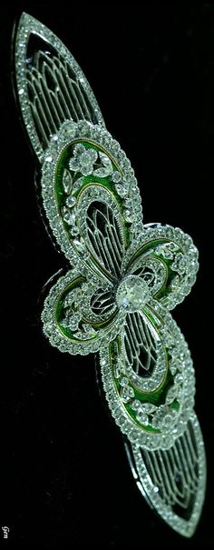 An Art Deco enamel and diamond brooch, European, 1920s. An openwork quatrefoil brooch with floral and foliate motifs set with old European- and rose-cut diamonds and decorated with green enamel, mounted in platinum and gold.