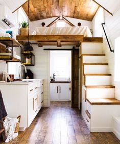 The kitchen features light granite counter tops, white cabinets with wood handles, open shelves, and of course a farmhouse sink.