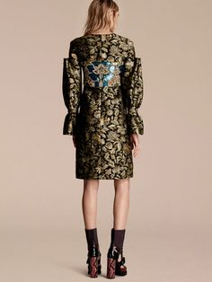 From the Burberry runway, a shift dress in textured fil coupé with a floral pattern echoing antique tapestries. Reminiscent of period-style silhouettes, sleeves are sculpted using large gathers and bell cuffs for dramatic fullness.