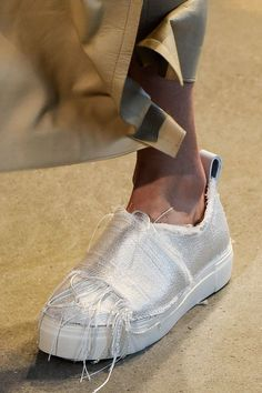 Good news! Your favorite rubber-soled slip-on sneakers aren't going anywhere by spring and summer. Only the new version will be a bit more luxe. Look for fabrics like satin and crafty details like the raw hems on this pair from Calvin Klein. Comfy and chic? Yes, please.Calvin Klein...