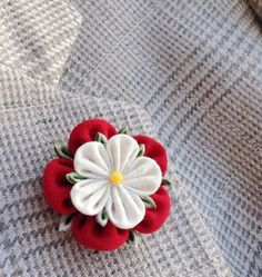 An elegant red and white Yorkshire rose flower lapel pin boutonniere for men and women, made in the Japanese tsumami kanzashi style! I used white linen and red wool for the flower and green cotton for the foliage of this ancient British symbol, sewed a mineral bead into the center, and mounted everything on a tie tack with a butterfly clutch back. Complements a suit, hat, cardigan, sport jacket, or blazer. Kanzashi flowers are made from folded fabric squares, one petal at a time. Originally…