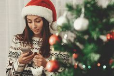Beautiful emotional brunette woman in red santa hat and reindeer sweater texting on her smartphone while decoration christmas tree with colorful ornaments, greeting card concept, space for text Reindeer Sweater, Brunette Woman, Smartphone, Apps, Trends, Santa Hat, Christmas Decorations, Christmas Tree, Flyer Design