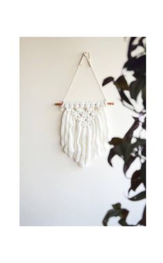 Macrame wall hanging with white wool yarn on a copper pipe.