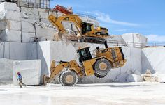 A front-end loader works to lift a marble stone at the Cervaiole quarry on Monte Altissimo on July 15, 2017.
