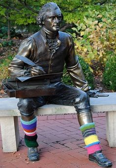 "From the Pinterest of Ann Hood, who is soon to be a WCDH resident. Much of her work centers around the healing and connection possible through knitting. The practice of decorating / covering public objects by knitting (and crocheting?) is called ""yarn bombing."" Here, Thomas Jefferson receives a pair of legwarmers. To me, yarn bombing has it all over Christos."