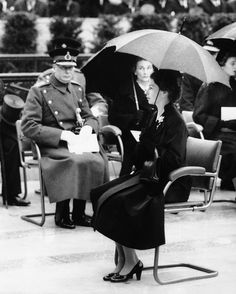 Queen Elizabeth II sits under an umbrella in heavy rain at the unveiling of the memorial statue to her father, King George VI, at the Carlton Garden in 1955. (AP Photo)
