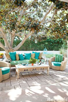 In the outdoor living room of a Malibu house designed by Todd Nickey and Amy Kehoe, a vintage sofa and coffee table mix with Janus et Cie chairs.