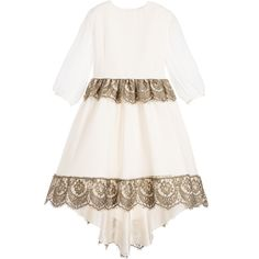 Girls luxurious, handmade ivory dress by Aristocrat Kids. Made from a layer of beautiful silk georgette, with sheer sleeves and fabric covered button fastenings. It has a fitted bodice, a full and voluminous skirt, with an under-layer of silk taffeta and tulle frills attached to the smooth cotton lining. It has a bronze lace trimmed waist with a sash to tie at the back. The elegant shaped hem is longer at the back with a matching lace trim. Super for bridesmaids and other special occasions.…