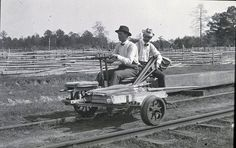 Two men riding a three-wheeled hand-operated velocipede (also called a Handcar or draisine) on a railroad track. They are conducting a level survey in Oklahoma's Indian Territory.