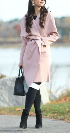 Such a pretty fall or winter outfit idea! Affordable blush pink winter coat over a black and white striped dress with black fleece-lined tights, black Steve Madden booties, and a black Vera Bradley satchel.