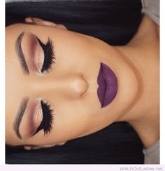 Gold, brown, glitter and black eye make-up with a purple lipstick