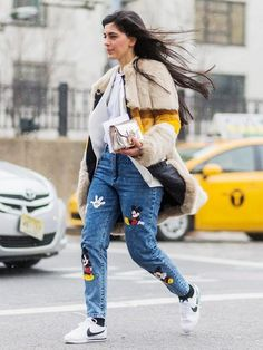 A striped fur coat is worn over a white shirt, white blazer, metallic clutch, Mickey Mouse jeans, and white Nike sneakers
