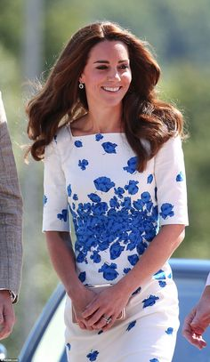 Well, white does show off a tan! Kate gripped a nude-coloured clutch purse. The glamorous Duchess also sported sapphire blue earrings encrusted with a circle of diamonds, which perfectly matched her frock