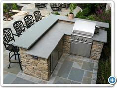 Outdoor fieldstone kitchen featuring raised stone bar counter, grill, refrigerator and trash encloser