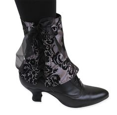 Our Ladies Silver Damask Spats are quite scandalous but well worth the risk of showing off. Bustle it up and bare your lower legs, these sultry spats put a luxurious layer of 'ooh-la-la' atop your boots and other footwear.Made from a richly appointed silver and black floral damask, the lining is swathed in plush black velveteen– these sensational spats are completely reversible at the wearer's whim. Metal grommets punctuate the front and lace up with black organza ribbon.Imported, two sizes…