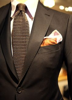 The monotone tie/jacket in a rich brown makes a typically casual knit tie a lot…