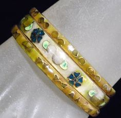 Vintage Chinese trio bangle bracelet set Bangles have a pale olive green backgorund with a flower design 1-5/16 inch wide bangles, 2-3/16 inch wide bangles, total width is 3/4 inch Signed with Chinese characters and the letter K Inside diameter is 2 5/8 inches Inside circumference is