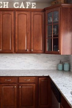 Cherry Cabinets with natural stone White marble tile. Love the white back splash and granite counter tops. It really makes for a light and bright kitchen against the dark cabinets.