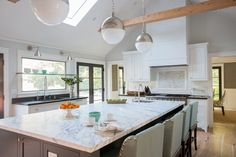 White kitchen with grey leather bar stools. Kitchen with white pendant lights over gray kitchen island with marble countertops