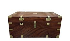 A British colonial travel chest in beautifully grained camphor wood, strengthened and simultaneously ornamented by brass mounts on the sides and all corners. The lid fitted with a hasp and two small recessed handles on the front panel. The front with two brass escutcheons and on the sides brass carrying handles. The chest opens to a fitted interior with a lidded document compartment and a lift out carrying tray.  Antique camphor chest from British colonial India – Bombay