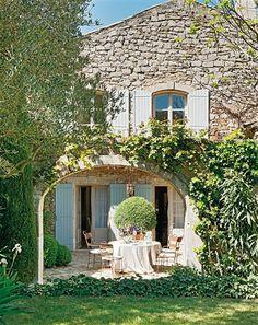 Fachada de piedra de casa rustica con mesa y sillas junto al arco