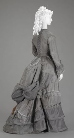 1870s walking suit via The Indianapolis Museum of Art. Notice the parasol pocket on the side of the dress. A dress that Tessa might have possibly worn due to the time period.