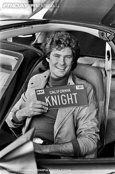 FR - Great pre-pilot press photo (note the gray jacket) of David Hasselhoff as Michael Knight holding up the famous KNIGHT plate inside K.I.T.T.