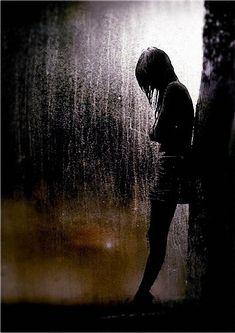 Фото Девушка стоит под дождем, прислонившись к дереву и сложив руки на груди