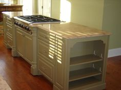 Green kitchen island with cooking area.