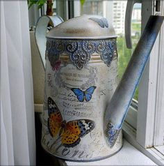 Watering can decorated in decoupage technique. The lake can be used for watering flowers and plants in the garden because the lake has a multiple